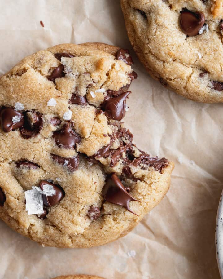 Close up of brown butter chocolate chip cookies with a bite missing.