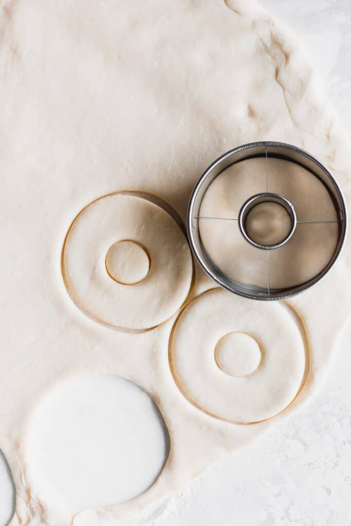 Taking a doughnut cutter to cut out doughnuts.