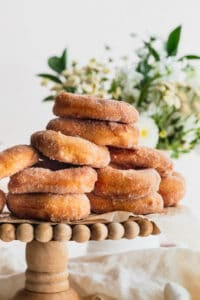 Stack of cinnamon sugar doughnuts on a cake stand.