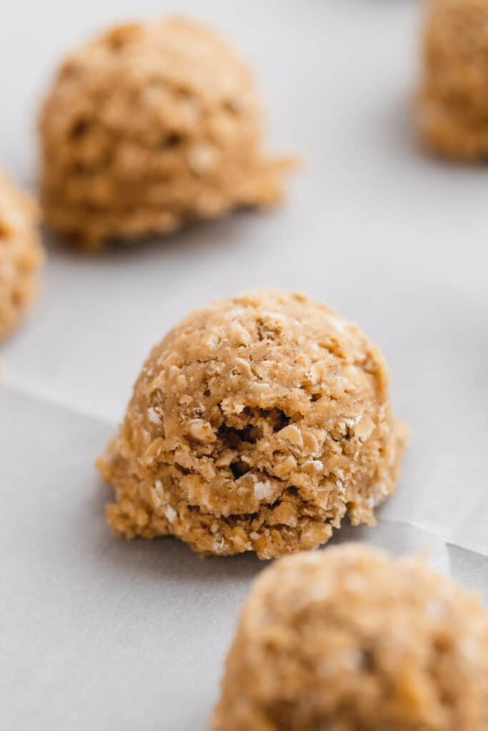 Scooped cookie dough balls on parchment paper.