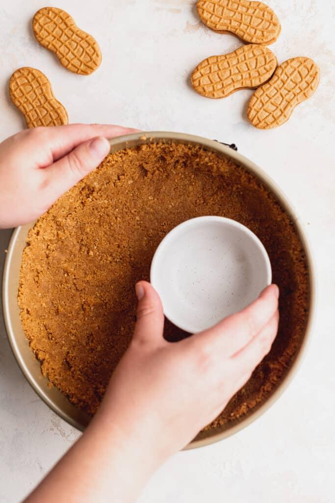 Pressing crumbs into pan.