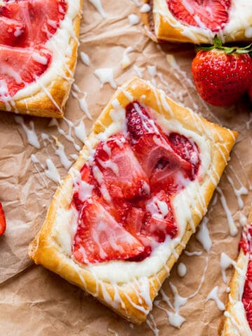 Strawberry danish on parchment paper with lemon glaze on top.