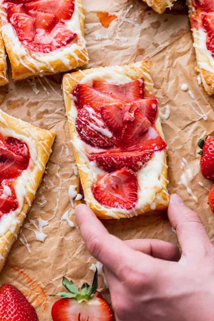 Hand coming to take strawberry danish.