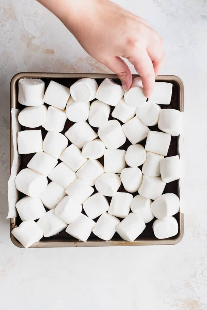 Marshmallows on top of the pan with a hand coming.