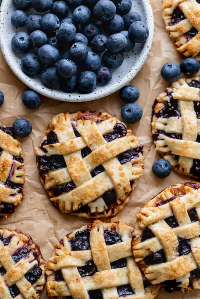Mini blueberry pies with plate of blueberries.