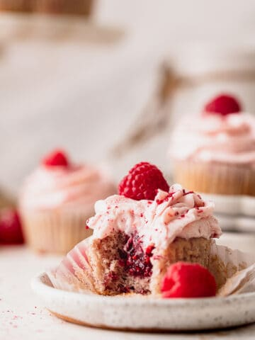 Bite missing from raspberry cupcakes.