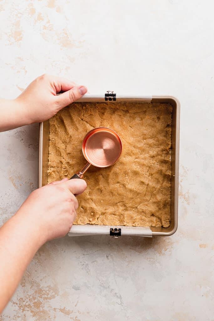 Pressing dough into pan.