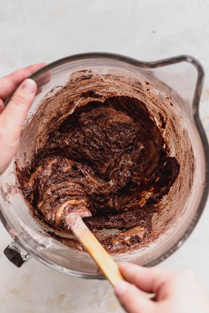 Mixing brownie batter in glass bowl.