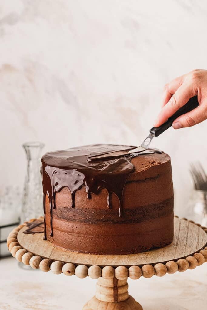 Spreading chocolate ganache on top of cake.