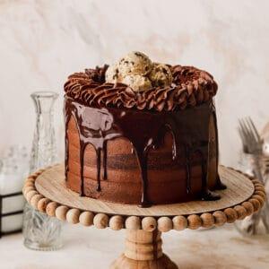 Chocolate brownie cookie cake on a cake stand.