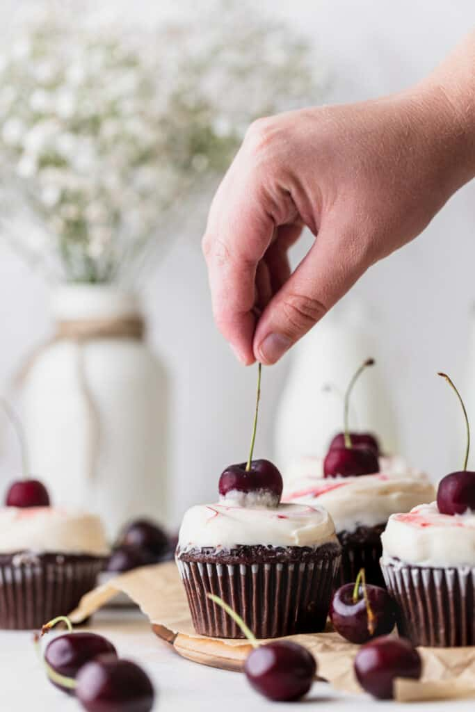 Topping the black forest cupcake with a cherry.