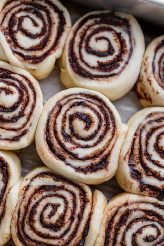 Raw cinnamon rolls in a pan.