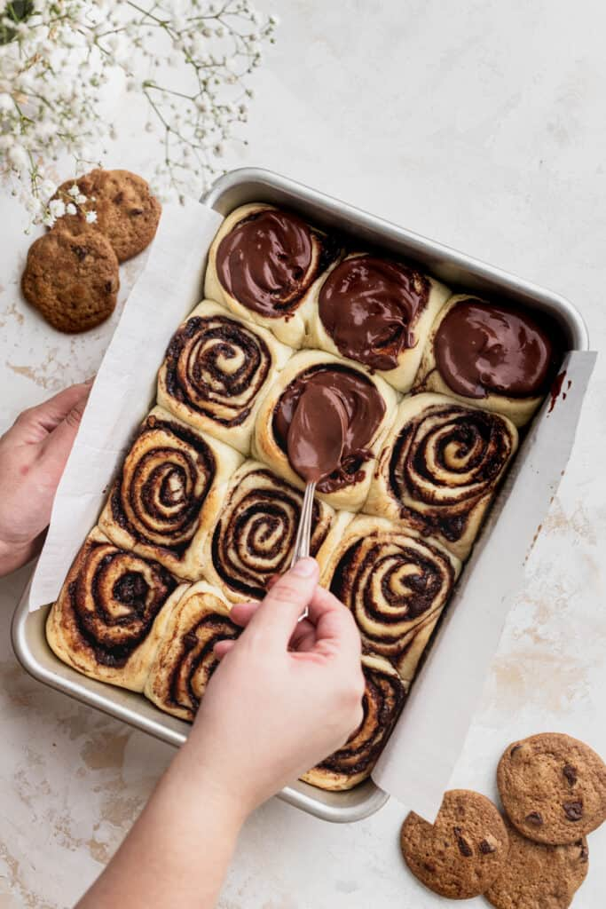 Spreading chocolate icing over the cinnamon rolls.