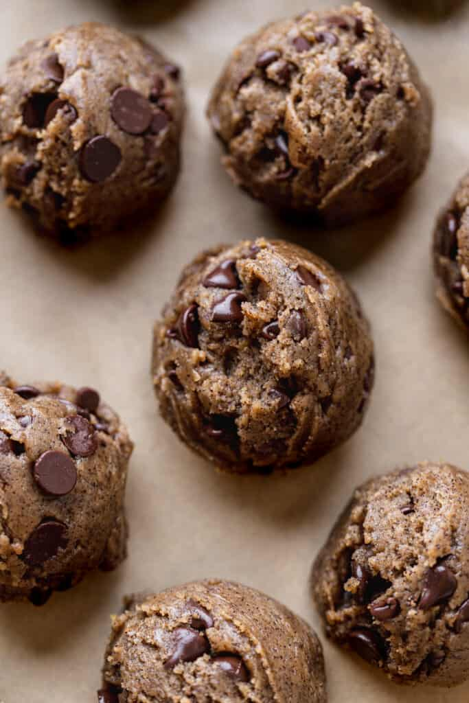 Cookie dough scoops on parchment paper.