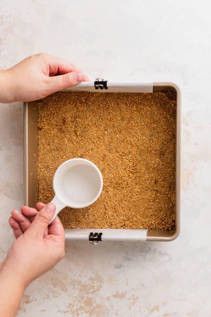 Compacting graham cracker crust into pan.