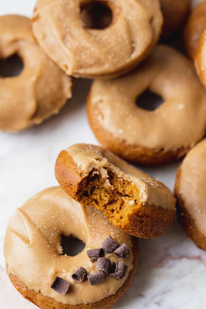 A bite missing from maple pumpkin donuts.