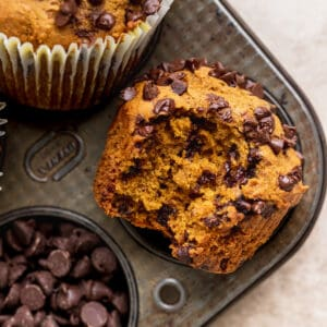 Bite missing from pumpkin chocolate chip muffins.