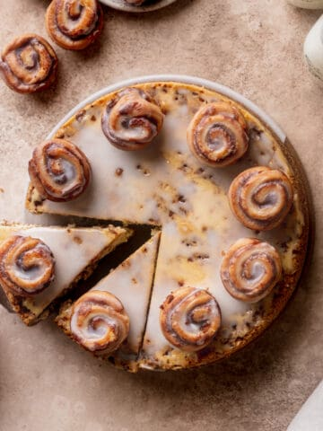 Cinnamon roll cheesecake pulling a slice out.