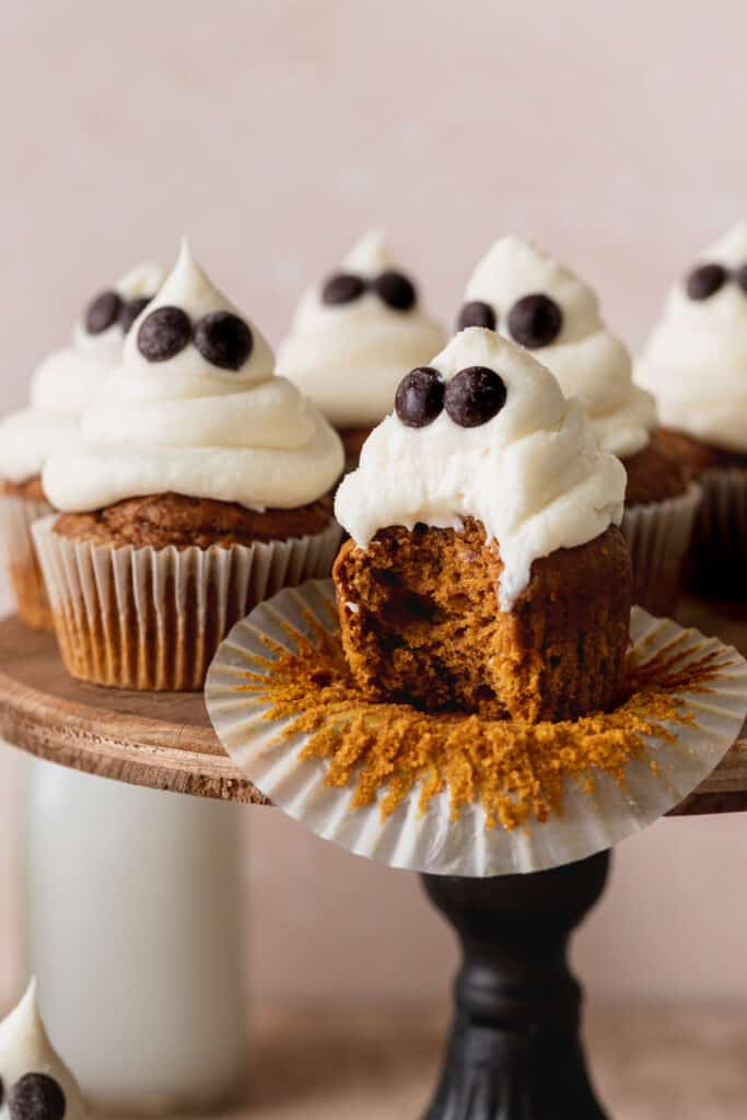 A bite missing from a pumpkin cupcake.