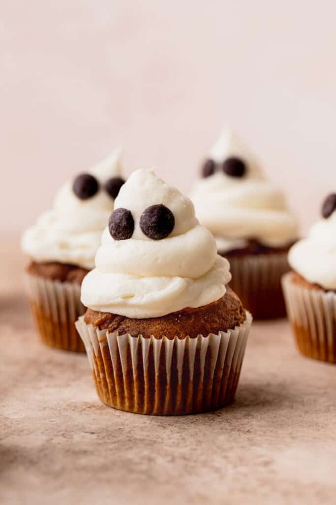 Pumpkin cupcake decorated to look like a ghost.