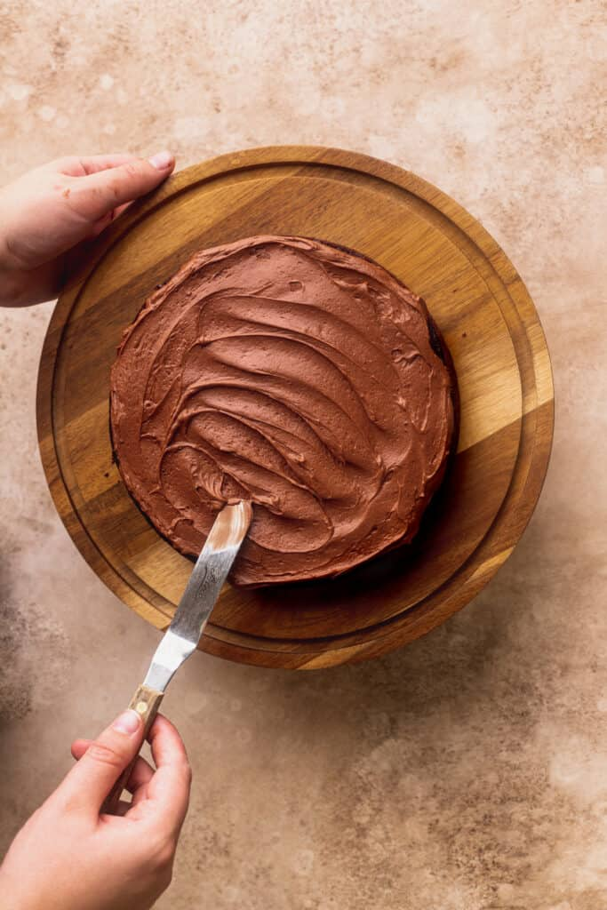 Spreading chocolate frosting on top of cake.