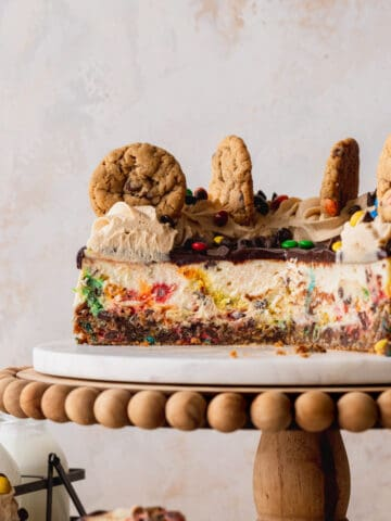 Monster cookie cheesecake cut in half on a cake stand.